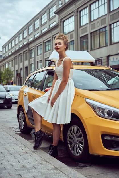 Белокурая девушка с развевающимися волосами на фоне улицы нью-йорка с такси. Premium Фотографии