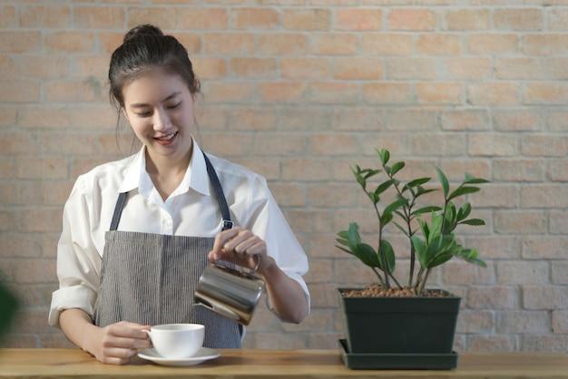 Стоящая молодая милая азиатская девушка-бариста кофе наливает кофе в чашку на столе Premium Фотографии