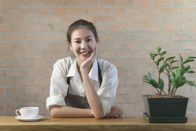 Стоящая молодая симпатичная азиатская девушка-бариста из кофе отдыхает на столе в баре Premium Фотографии