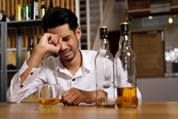 パブに座っている男は、彼の悲しみのために泣いていて、アルコールを飲むことによってそれを忘れたいと思います。 Premium写真