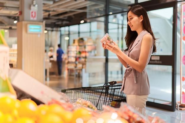 アジアの美しい少女は、スーパーで果物を選んでいます。 Premium写真