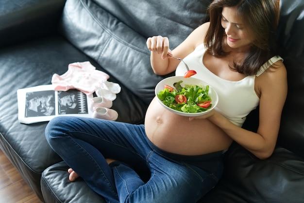 ソファーに座っていた妊娠中の女性は彼女の手でサラダボウルを持っています。彼女の将来生まれたベビードレス Premium写真