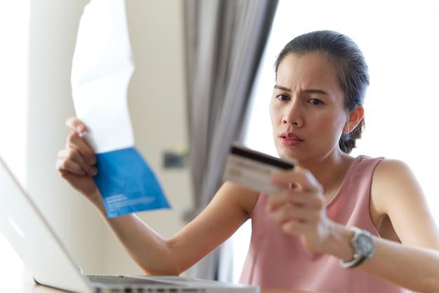Усиленная азиатская женщина держа кредитную карточку и счеты чувствуя беспокойство о деньгах находки для того чтобы оплатить задолженность по кредитной карточке и все счета займа. Premium Фотографии