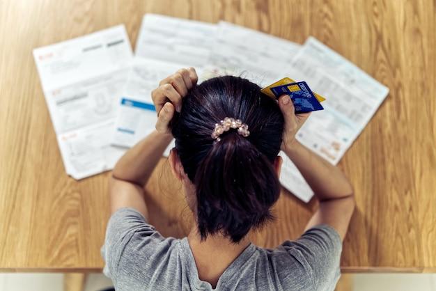 Взгляд сверху усиленных молодых сидя азиатских рук женщины держа головное беспокойство о деньгах находки для того чтобы оплатить задолженность по кредитной карте и все счета по кредиту. Premium Фотографии