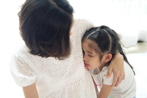アジアの若い女の子は彼女の両親の隣で泣いています、そして、彼女の母親は頭に優しく触れて慰めています。 Premium写真