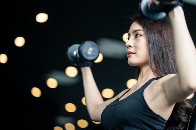 両方の手でダンベルを持ち上げるスポーツウェアで美しいアジアのセクシーな女の子。 Premium写真