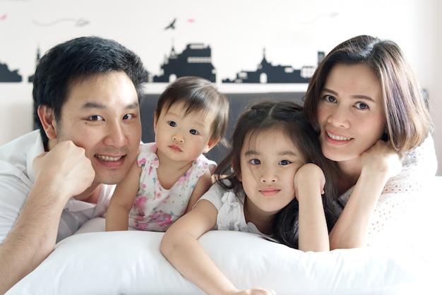 アジアの父、母、姉、小さな赤ちゃんが寝室のベッドで笑顔で横になっています。 Premium写真
