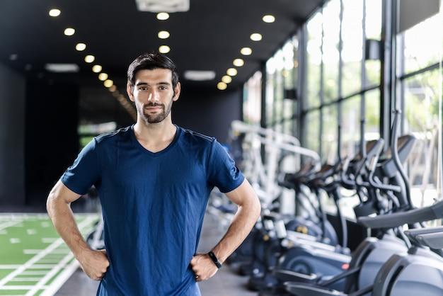 青い色のスポーツウェアに立って、ジムやフィットネスクラブで腰に手を入れてひげを持つハンサムな白人男性。 Premium写真