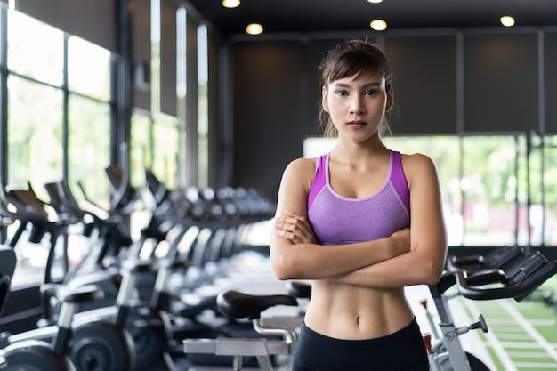 Довольно азиатская девушка с шестью пачками в фиолетовый цвет спортивной одежды стоя и скрещивание оружия в тренажерном зале или фитнес-клубе. Premium Фотографии