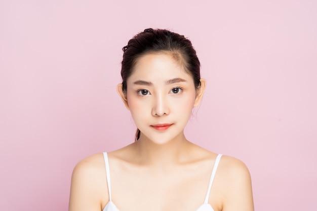 Красивая молодая азиатская женщина с чистым свежим белым положением кожи Premium Фотографии