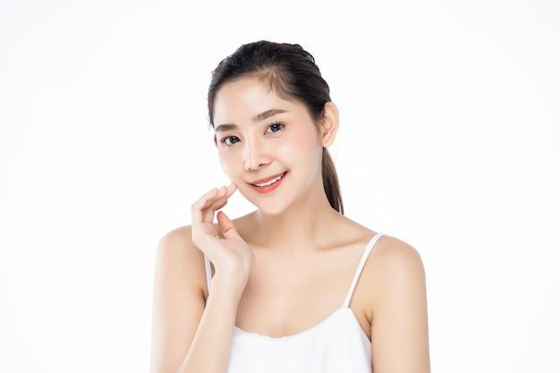 きれいな新鮮な白い肌の美しさのポーズでそっと自分の顔に触れる美しい若いアジア女性。 Premium写真