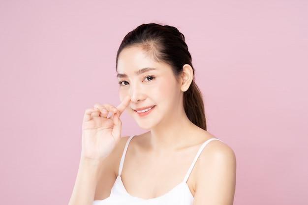美容ポーズでそっと彼女自身の鼻に触れる清潔で新鮮な白い肌を持つ若いアジア女性 Premium写真