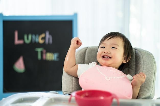 自宅で笑顔でスイカを保持している座席を給餌赤ちゃん高椅子に若いかわいい子供は、食事甘い果物を食べて、幸せを笑ってお楽しみください。 Premium写真