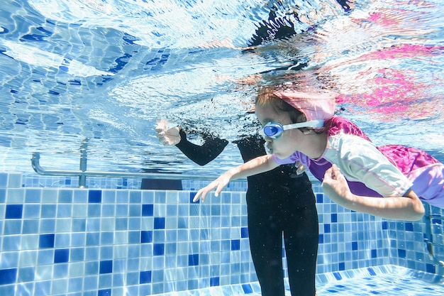 Подводная молодая маленькая милая девушка плавает в бассейне с ее учителем плавания. Premium Фотографии