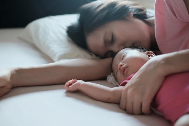 アジアの母親がベッドで寝ている彼女の生まれたばかりの赤ちゃんを抱き締めます。 Premium写真