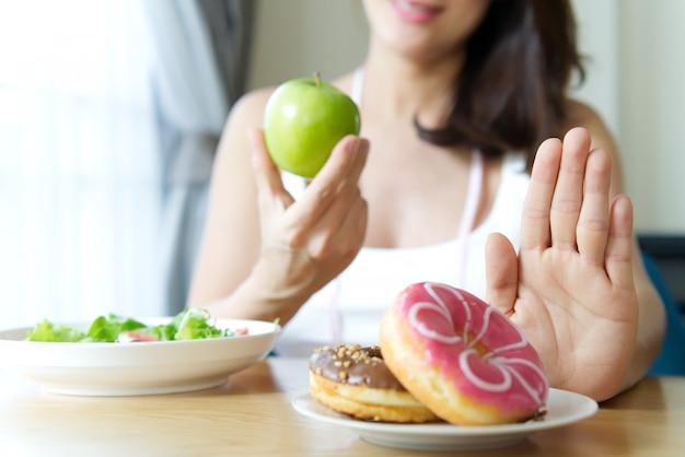 Молодая девушка, отказ от нездоровой пищи, такие как пончики. Premium Фотографии