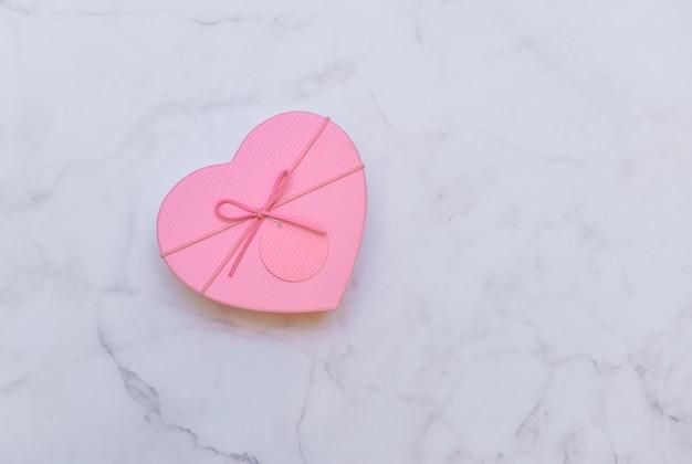 Розовая упаковка для подарка в форме сердца на мраморном светло-сером фоне, вид сверху. день святого валентина, любовь, тема подарков. Premium Фотографии