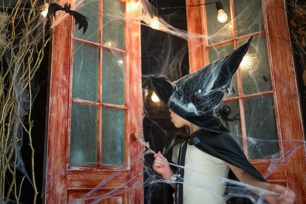 Кавказский мальчик в карнавальном костюме волшебника распутывает паутину на декоре хэллоуина Premium Фотографии