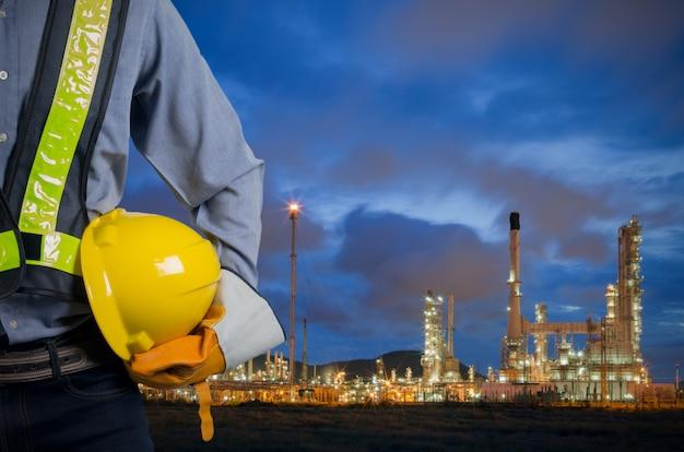 石油精製所で黄色いヘルメットを保持しているエンジニア。 Premium写真