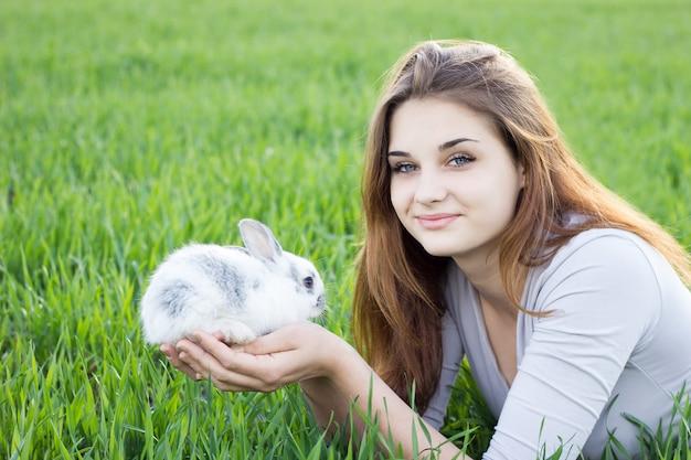 緑の牧草地でウサギを保持している女の子。 Premium写真