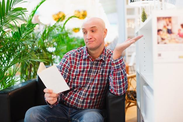 Человек сидит в кресле в светлой квартире с удивлением читает книгу Premium Фотографии