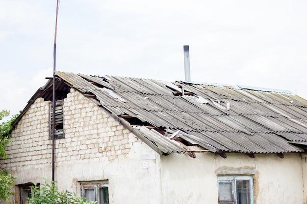 Сломанная крыша после урагана, дом в деревне, разрушенная крыша жилого дома Premium Фотографии