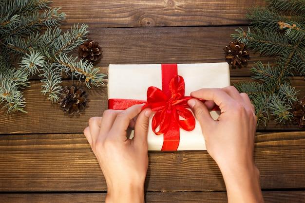 手は、モミの枝と円錐形の木製の背景にクリスマスプレゼントを開梱します。 Premium写真