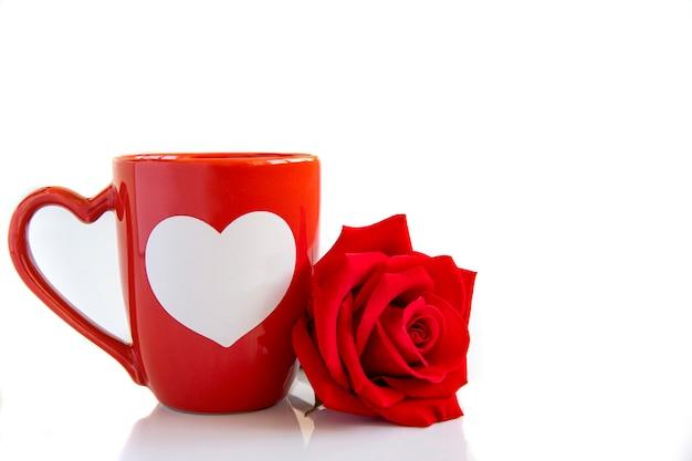 コーヒーマグと赤いバラ Premium写真