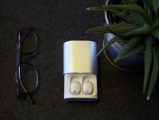 充電ケースに白いワイヤレスヘッドフォンのフラットレイアウトビュー。 Premium写真