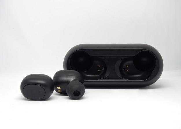 充電ケース近くの黒いワイヤレスヘッドフォン。 Premium写真