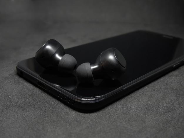 暗い背景に携帯電話を持つワイヤレスヘッドフォン。 Premium写真