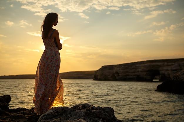 美しい海の景色と夕日、崖の上、美しい空と海の上の少女のシルエットの背景の上の少女 Premium写真