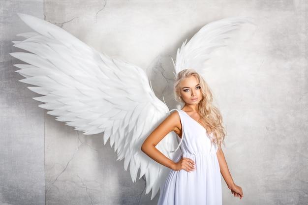 白い背景の上の白い翼を持つ美しい女性 Premium写真