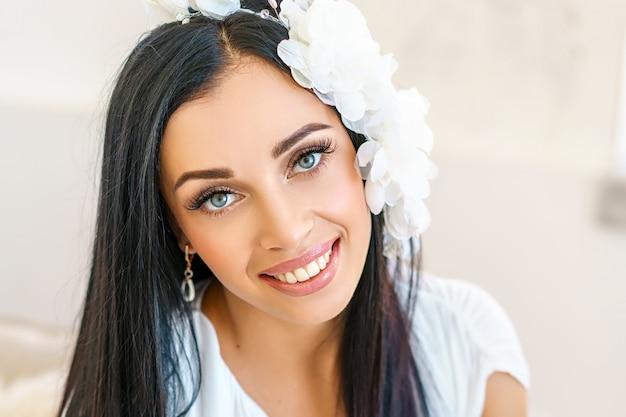 豪華な白いドレスの美しい若い女性。白いスタジオで撮影します。 Premium写真