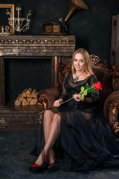 赤い靴で椅子に座っているコルセットと黒のドレスで美しい女性 Premium写真