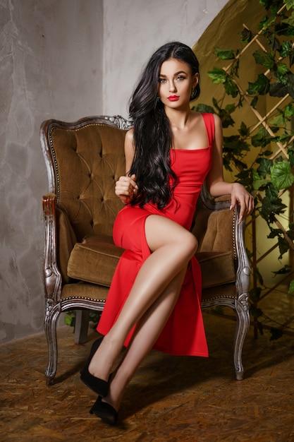 赤いドレスを着た美しい女性が椅子に座っています。 Premium写真
