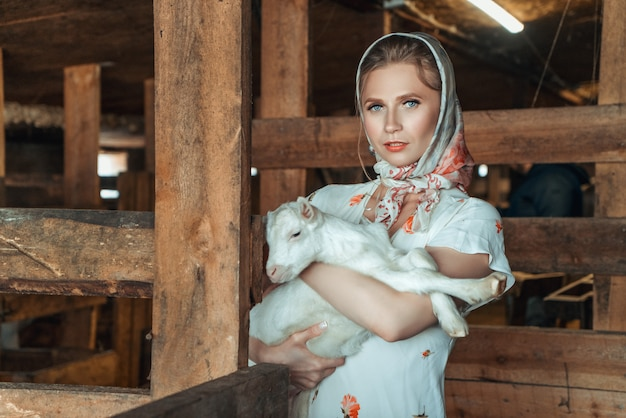 彼女の腕の中で小さなヤギを保持している農場の女性 Premium写真