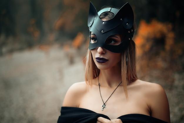 黒い猫のマスクを着た女性が自然の背景に立っています。 Premium写真