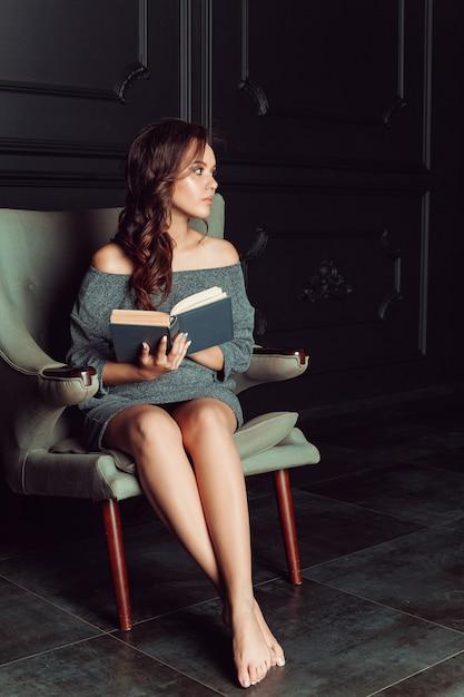 美しい女性の椅子に座って本を読む Premium写真