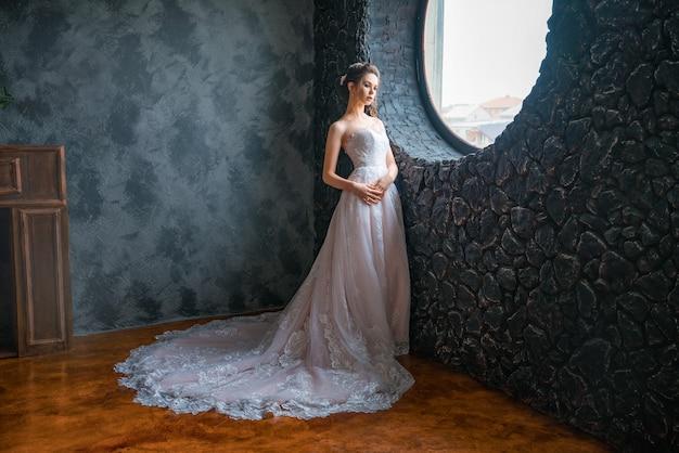 窓際の長いドレスの美しい花嫁 Premium写真