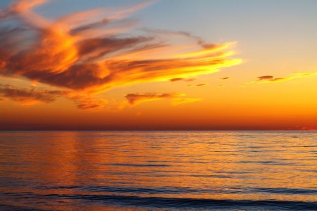 海、夕焼けの鮮やかな色の上空で美しい夕焼け雲。 Premium写真