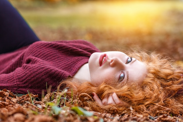 Рыжая девушка лежит в опавшей желтой листве Premium Фотографии