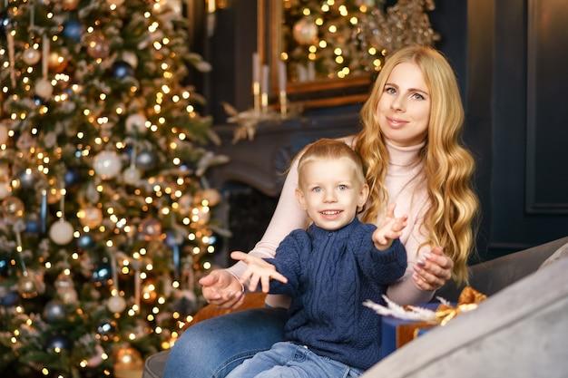 ママと息子のクリスマスツリー、休日の概念のポーズで座っています。 Premium写真
