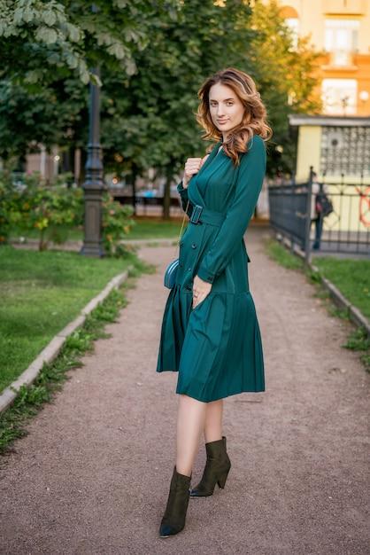 緑のドレスで散歩に美しい若い女性。 Premium写真