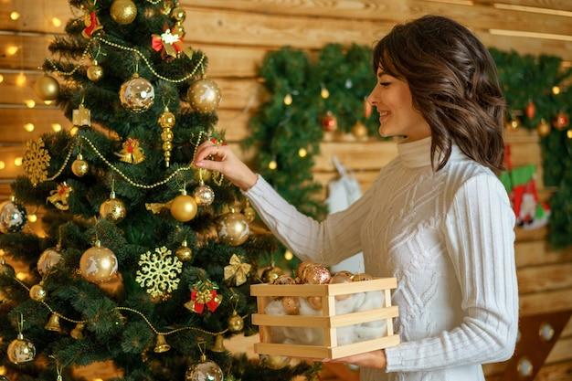 美しい幸せな女はクリスマスツリーをドレスアップ Premium写真