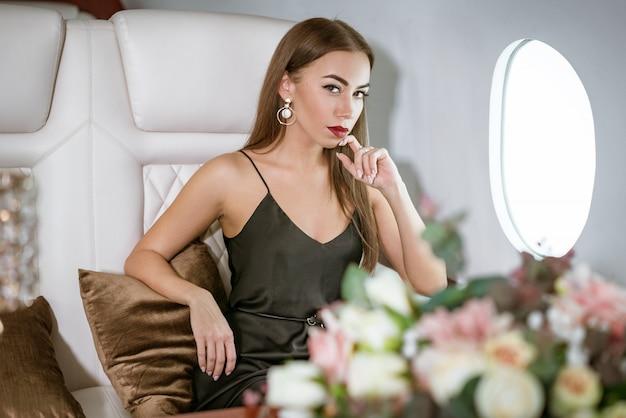 プライベートファーストクラスの飛行機で美しい金持ちの女 Premium写真