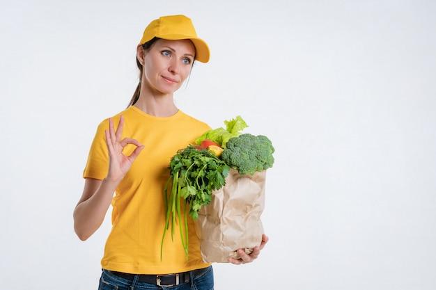 Женщина в желтой одежде, доставляя пакет с едой, на белом фоне Premium Фотографии