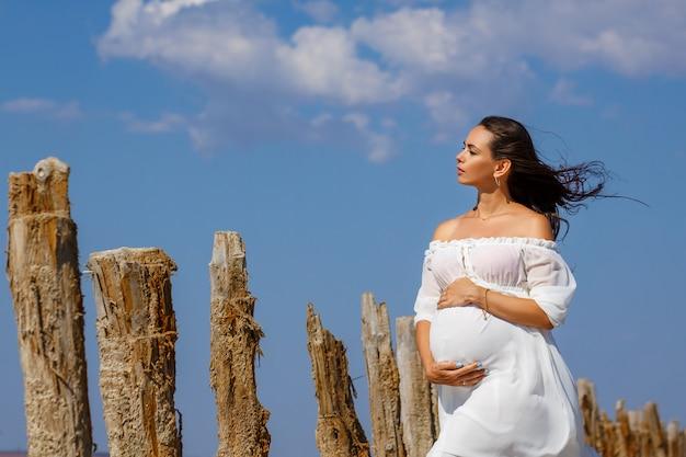 Красивая молодая беременная женщина, стоя в природе на соленое озеро. Premium Фотографии