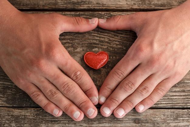手と赤いハート、木製の背景、健康の概念の上に横たわる。 Premium写真