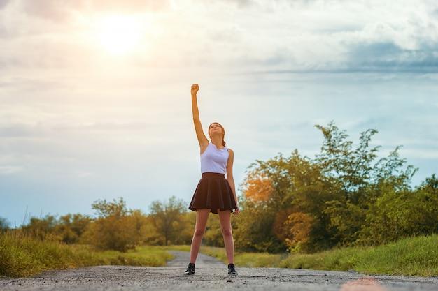 彼女の手を挙げろ、成功のコンセプトで道路上に立っている若い女の子。 Premium写真
